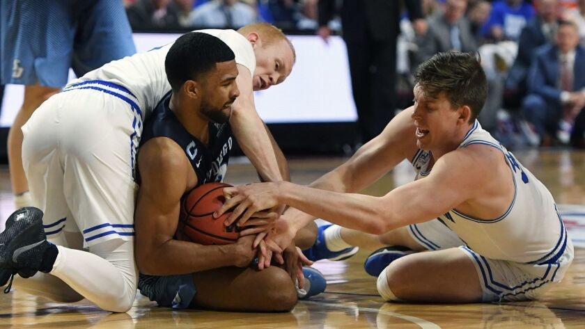 TJ Haws of BYU (left) fouls USD's Isaiah Wright (center) as Dalton Nixon reaches for the ball in Saturday's WCC Tournament game.