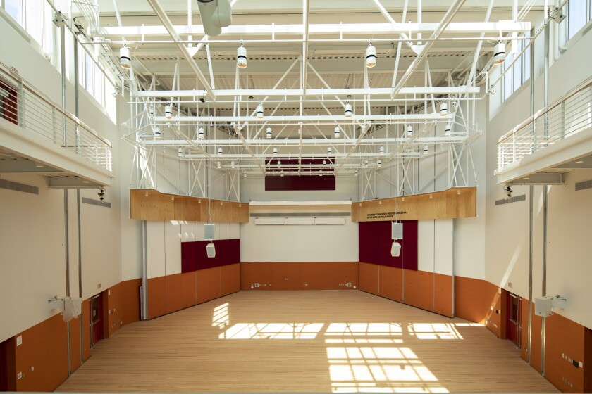A view of an empty performance hall with sunlight streaming from a skylight above