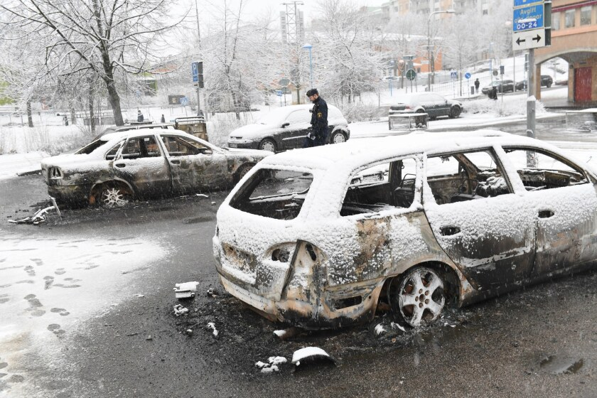 A police officer takes notes at a burnt car in the suburb of Rinkeby outside Stockholm, Sweden on Feb. 21.