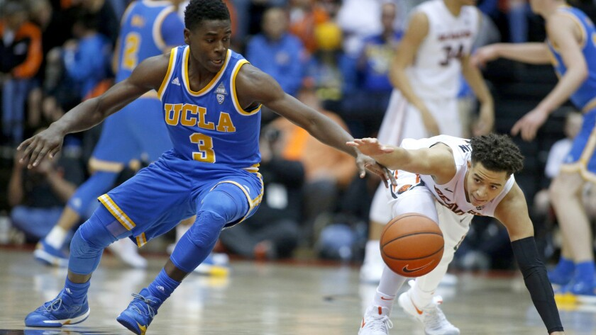 UCLA guard Aaron Holiday and Oregon State guard JaQuori McLaughlin chase after a loose ball during the first half Friday night.