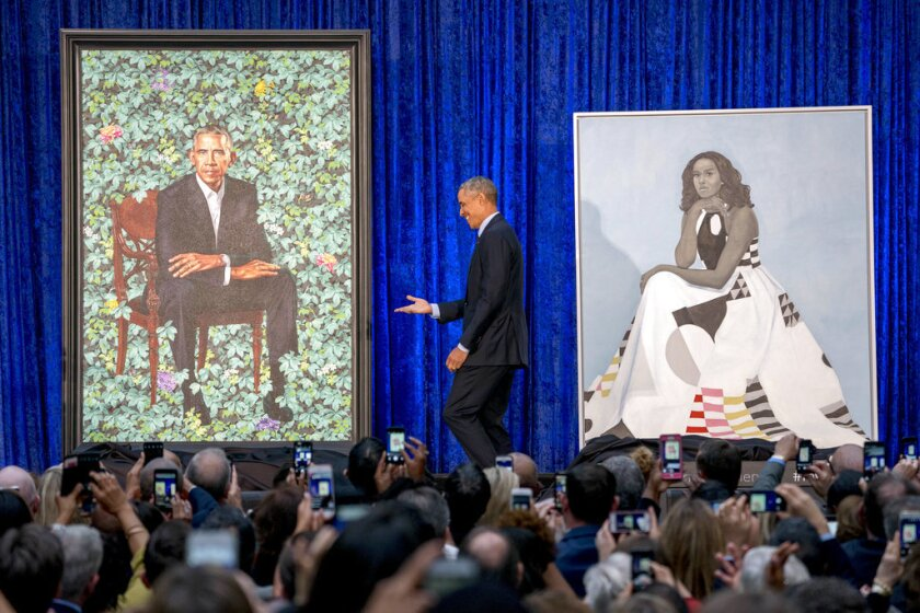 Former President Barack Obama, center, stands on stage during the unveiling of the Obama's official portraits at the Smithsonian's National Portrait Gallery, Monday, Feb. 12, 2018, in Washington.