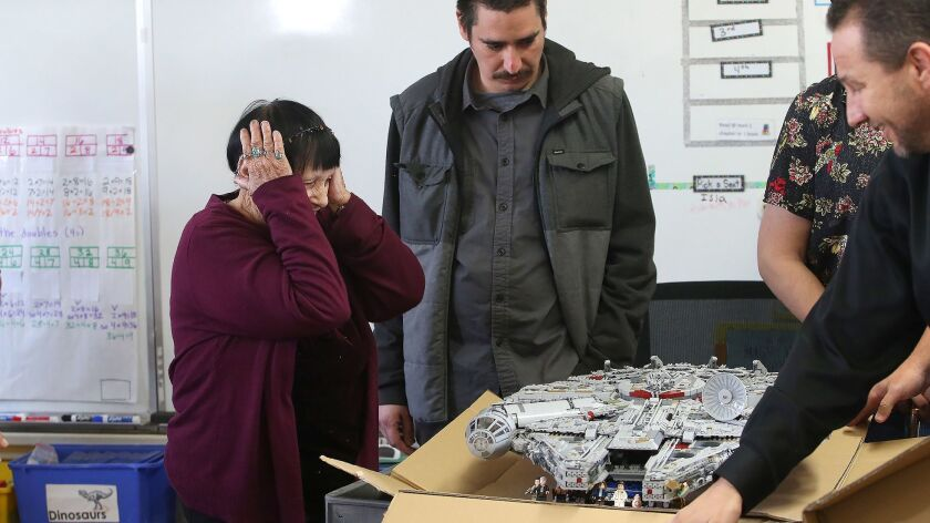 Instructional assistant Jeanna Bassett reacts upon seeing her lego millennium falcon starship unveil