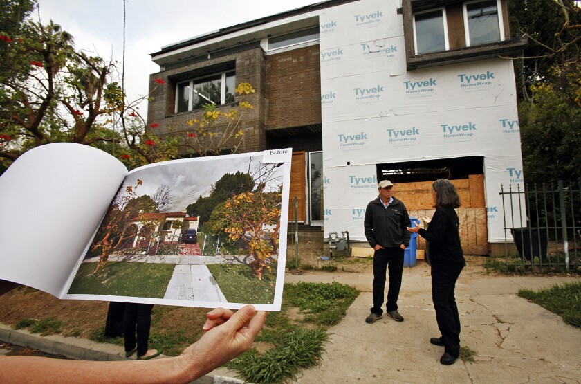 "Traci Considine holds a ""before"" photo of a home under construction in her Faircrest Heights neighborhood that she believes is an example of mansionization on March 14, 2014."