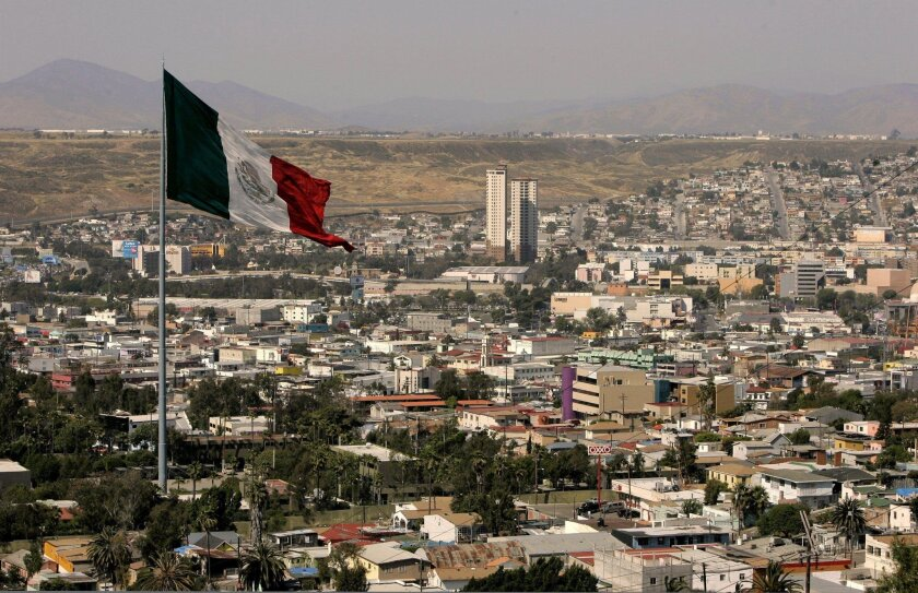 High angle view of the Tijuana looking east from the end of a street in Colonia Mexico. The large Mexican flag is flying at the city's Army base.