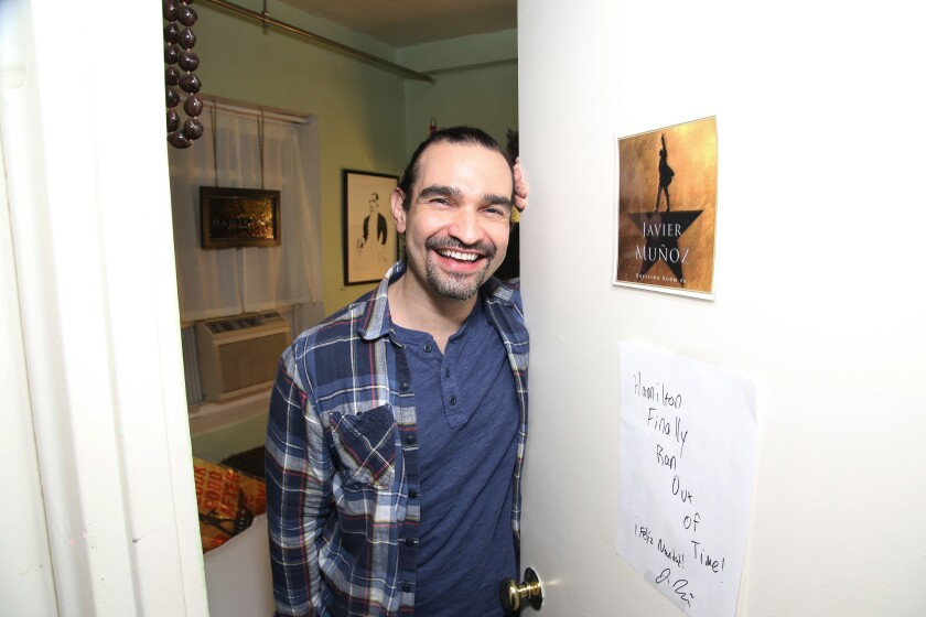 """""""Hamilton"""" star Javier Muñoz smiles while holding open a door at Richard Rodgers Theatre in New York in 2016"""