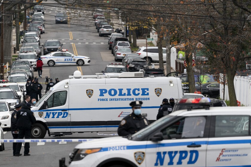 Police vehicles are parked near the scene of a shooting in The Bronx, Friday, Dec. 4, 2020 in New York. A suspect in the shooting of a state trooper in Massachusetts was killed during a shootout with U.S. marshals in New York City early Friday that left two of the officers wounded. (AP Photo/Mark Lennihan)