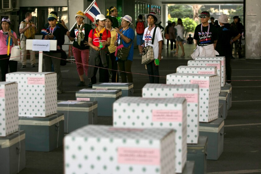 Anti-government protesters stand by empty ballot boxes as they block a district office in an attempt to stop the elections Sunday in Bangkok, Thailand.