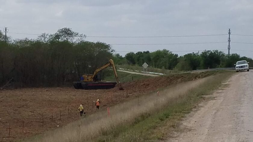 Border Patrol contractors in Texas' Rio Grande Valley survey land Monday where brush has been cleared for a border fence.