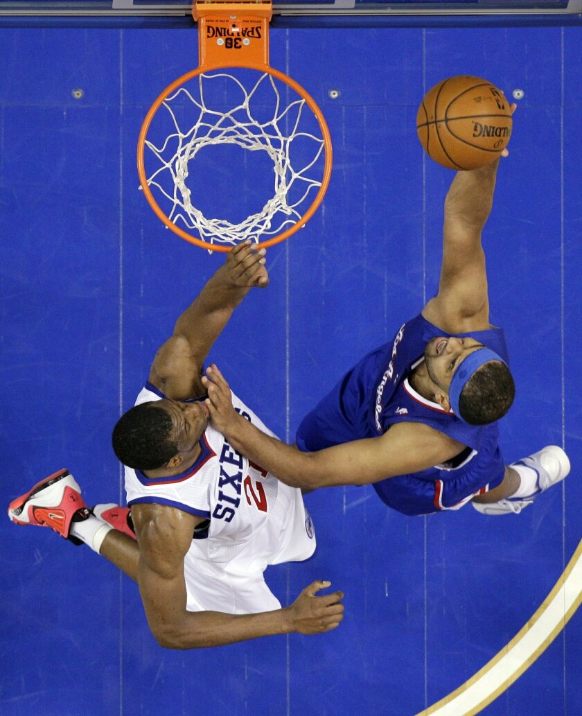 Los Angeles Clippers' Jared Dudley, right, goes up for a shot against Philadelphia 76ers' Thaddeus Young during the first half of an NBA basketball game, Monday, Dec. 9, 2013, in Philadelphia. (AP Photo/Matt Slocum)