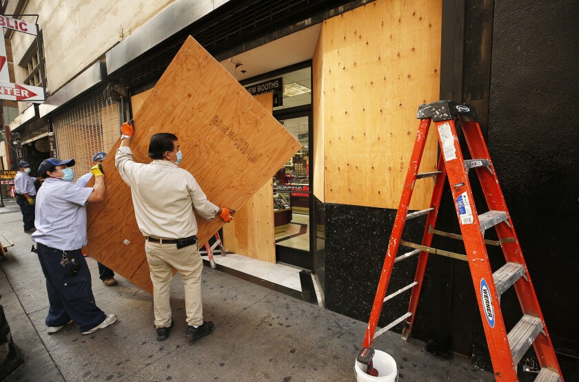 Workmen build a plywood wall at the storefront of a complex of jewelry stores in downtown L.A. ahead of election day.
