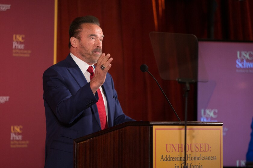 Former Gov. Arnold Schwarzenegger stands and gestures at a lectern with the USC logo in the background.