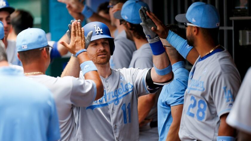 Dodgers' Logan Forsythe (11) celebrates with teammates after hitting a two-run home run in the third inning against the Cincinnati Reds.