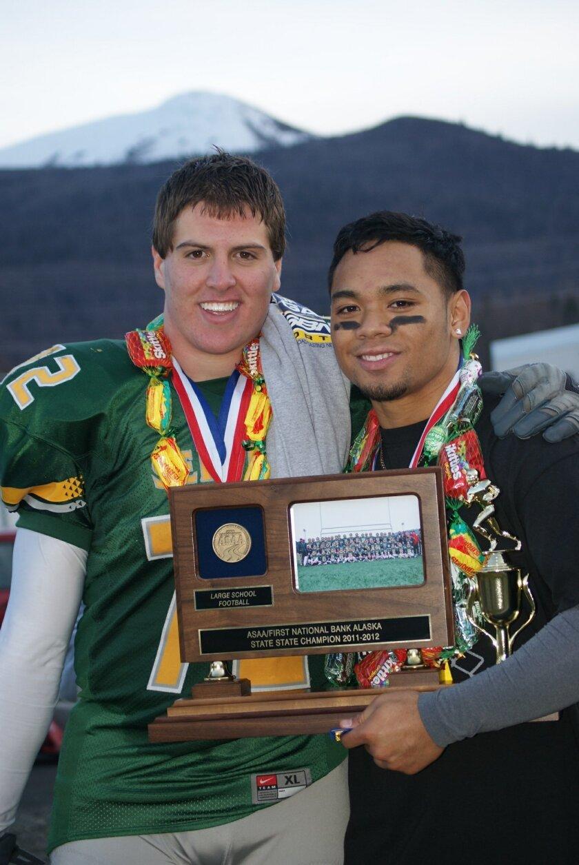 Jeff Overbaugh (left) celebrates 2011 Alaska state high school football championship with Service High teammate Matthew Ilalio.