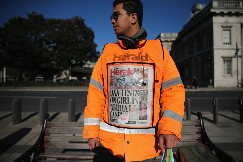 A newspaper vendor wears a vest displaying front page of The Herald in Dublin, Ireland. Irish authorities were waiting for DNA test results in relation to a blond girl removed from a Roma family in Dublin, days after a similar case in Greece.