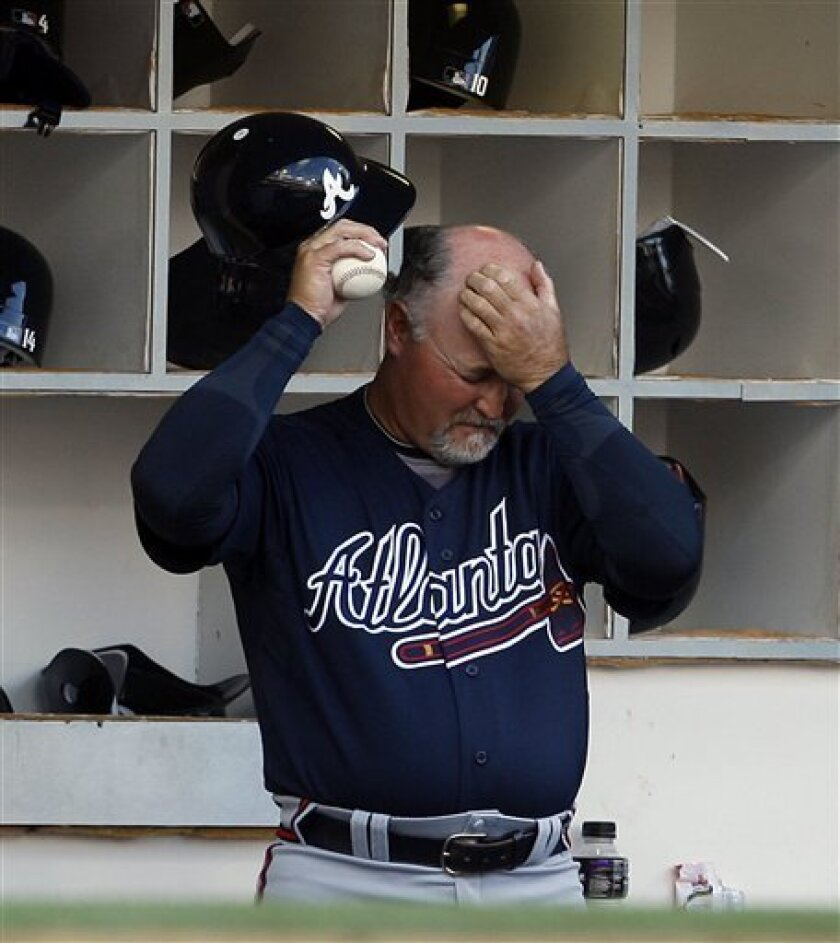 Atlanta Braves coach Glenn Hubbard rubs his head while standing in the dugout during the fourth inning in which the San Diego Padres scored 10 runs during a baseball game Monday April 12, 2010 in San Diego.  (AP Photo/Lenny Ignelzi)