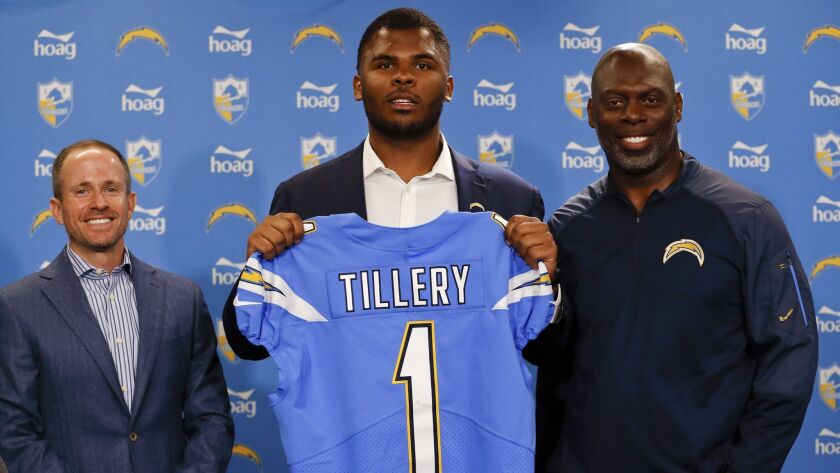 Los Angeles Chargers NFL football defensive tackle Jerry Tillery, center, poses with a jersey alongs