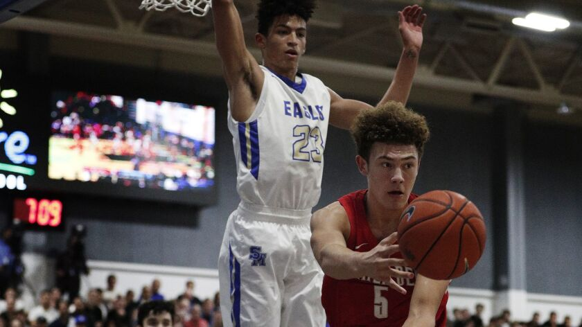 Mater Dei's Devin Askew passes after driving down the lane against Santa Margarita's Max Agbonkpolo (23) during the first half of their game Wednesday.