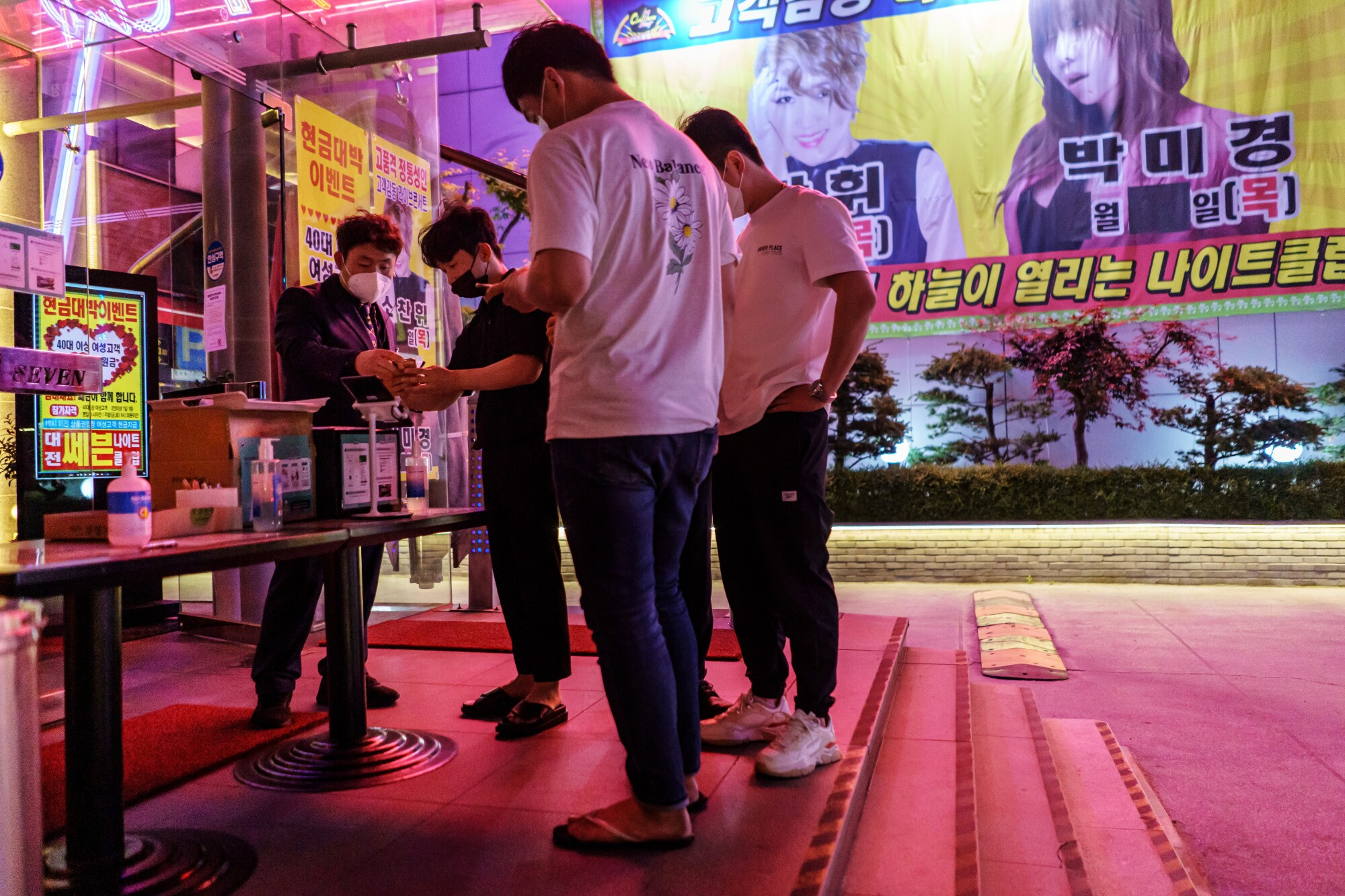 Bouncers ask patrons to scan QR codes on their smartphones at a South Korean nightclub.