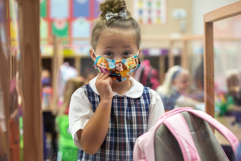 A second grader adjusts her face mask at Christian Unified on Monday, Aug. 24, 2020 in El Cajon.