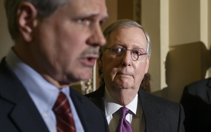 Senate Majority Leader Mitch McConnell, R-Ky., center, listens as Sen. John Hoeven, R-N.D., sponsor of the Keystone XL pipeline bill, talks with reporters after winning a critical procedural vote on the Keystone XL Pipeline bill, at the Capitol in Washington, Thursday, Jan. 29, 2015. The Republican