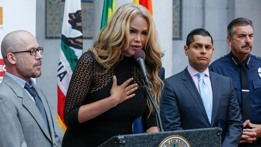 Transgender activist Maria Roman, with her fiance, Jason Taylorson, left, addresses the media during an Equality California press conference at Los Angeles City Hall on Friday.
