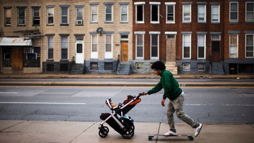 A man rides a skateboard and pushes his son in a stroller along a sidewalk in Baltimore on May 11.