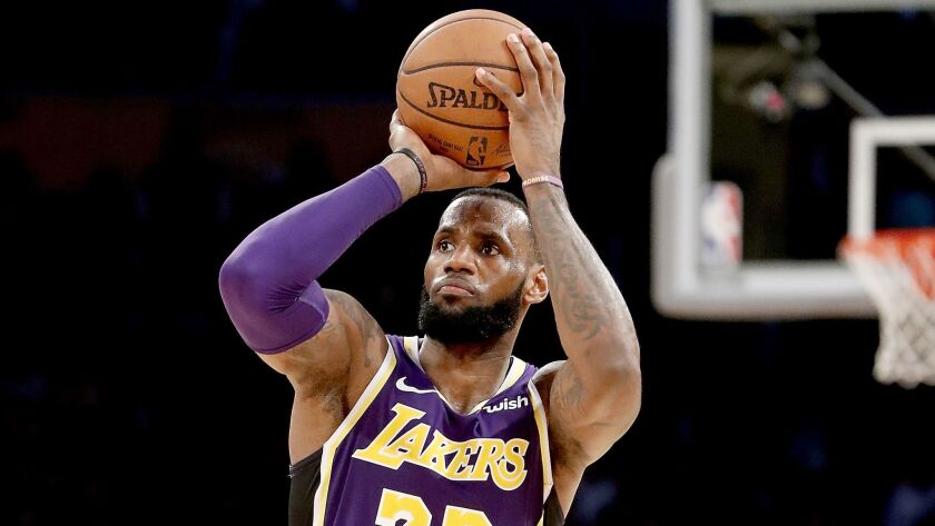 LeBron James of the Lakers shoots and scores a three-pointer against the San Antonio Spurs on Dec. 5, 2018, at Staples Center.