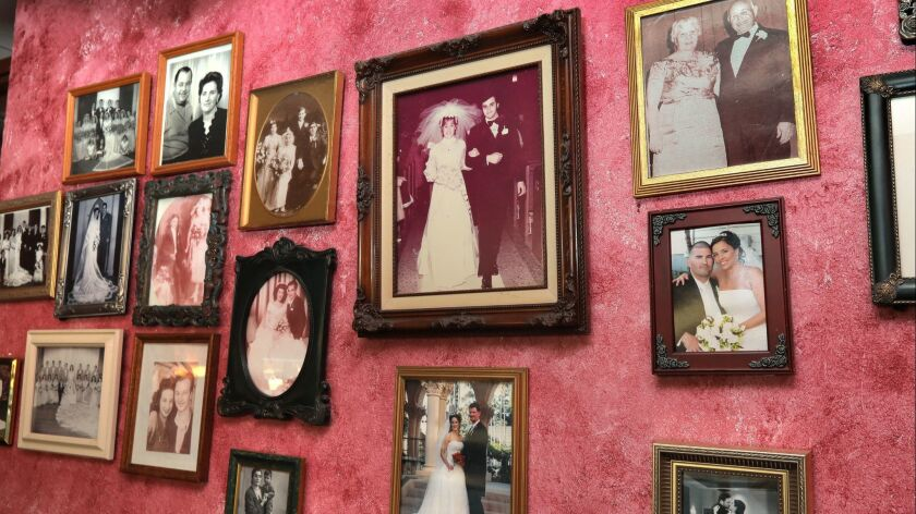 Family photos cover the walls at Feliccia's Italian Restaurant and Deli that's closing December 13th. after 40 years. In the middle is a wedding portrait of owners Sam and Nina Feliccia.