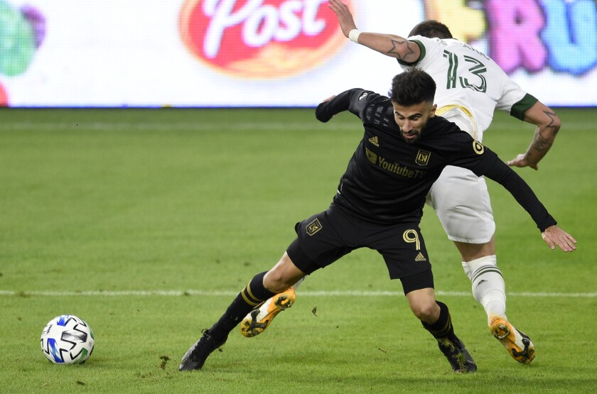 Los Angeles FC forward Diego Rossi, front, and Portland Timbers defender Dario Zuparic battle for the ball.