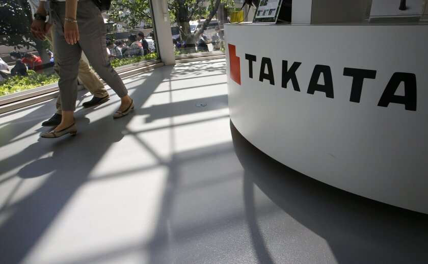 FILE - In this May 4, 2016, file photo, visitors walk by a Takata Corp. desk at an automaker's showroom in Tokyo. A U.S. Senate report says at least four automakers are selling new vehicles that have potentially deadly Takata air bag inflators. The report by Commerce Committee Democrats says some 2