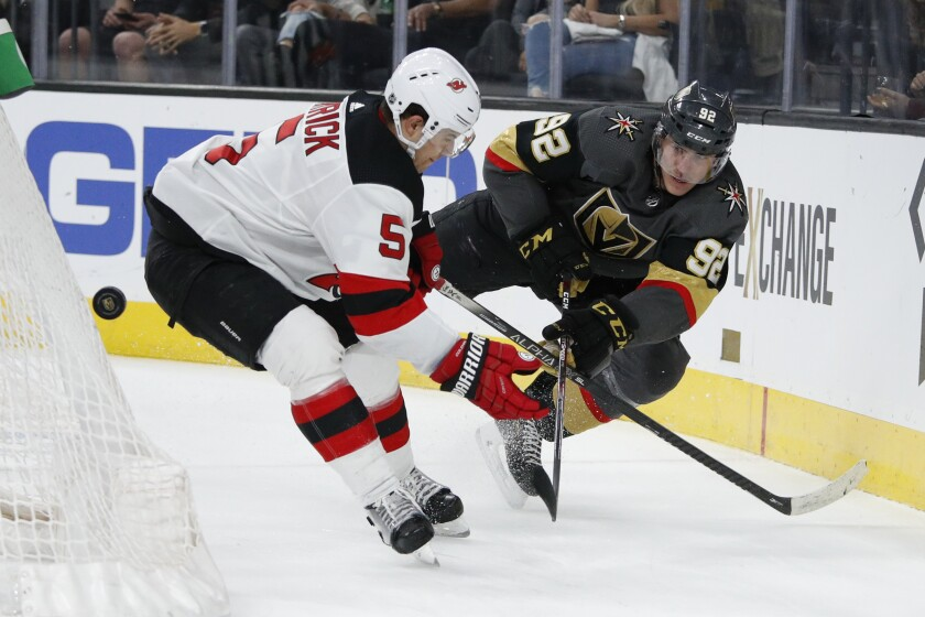 Vegas Golden Knights left wing Tomas Nosek (92) vies for the puck with New Jersey Devils defenseman Connor Carrick (5) during the second period of an NHL hockey game Tuesday, March 3, 2020, in Las Vegas. (AP Photo/John Locher)