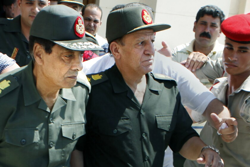 FILE - In this Sept. 16, 2011, file photo, Egypt's then military ruler field marshal Hussein Tantawi, left, and Sami Annan, then Egyptian chief of staff of the armed forces, are surrounded by military policemen as they attend the funeral of Khaled Abdel Nasser, the son of Egypt's late president Gamal Abdel Nasser, in Cairo, Egypt. Tantawi, the Egyptian general who ruled the country following the Arab Spring uprising that removed longtime autocrat Hosni Mubarak, died on Tuesday, Sept. 21, 2021, Egypt's presidency said. He was 85. (AP Photo/Amr Nabil, File)