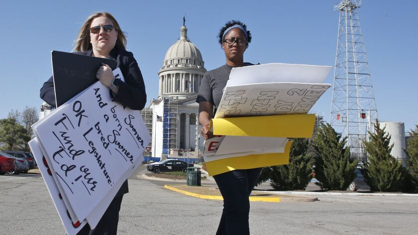 Kara Walk, left, assistant principal in the Putnam City School District of Oklahoma City and Ivana Beatty, assistant principal in the Oklahoma City Public Schools, gather protest signs.