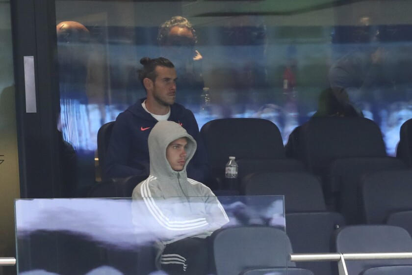 Tottenham's Gareth Bale, backfround, sits on the stands during the English Premier League soccer match between Tottenham and Newcastle at the Tottenham Hotspur Stadium in London, Sunday, Sept. 27, 2020. (Clive Rose/Pool via AP)