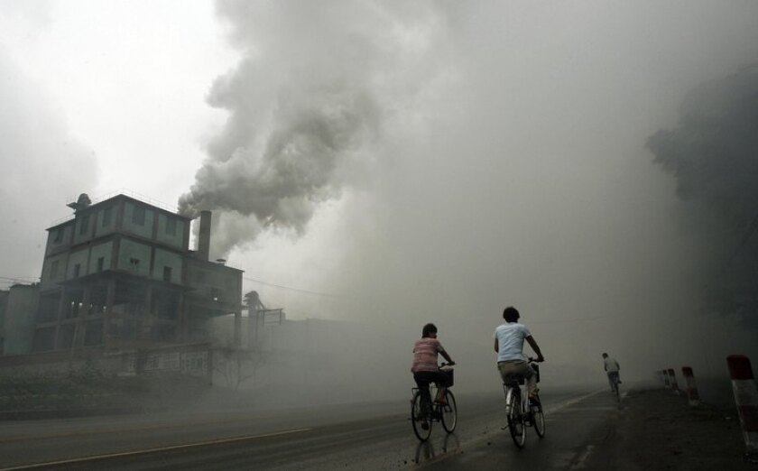 Cyclists pass a factory in Beijing in 2006