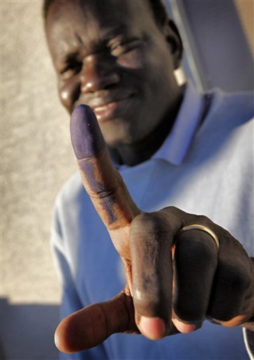 FILE - In this Nov. 26, 2010 file photo, James Chol, a 31-year-old Lost Boy from Southern Sudan who lives in Phoenix, shows his ink stained finger at a voter registration facility in Glendale, Ariz. Hundreds of survivors of Sudan's civil war now living in the U.S. will vote on Sunday to decide whether Southern Sudan secedes from the north, creating the world's newest country and giving South Sudan independence. (AP Photo/Matt York, File)
