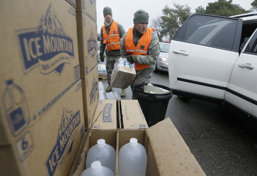 Members of the Michigan National Guard load bottled water at a fire station on Jan. 28 in Flint, Mich.