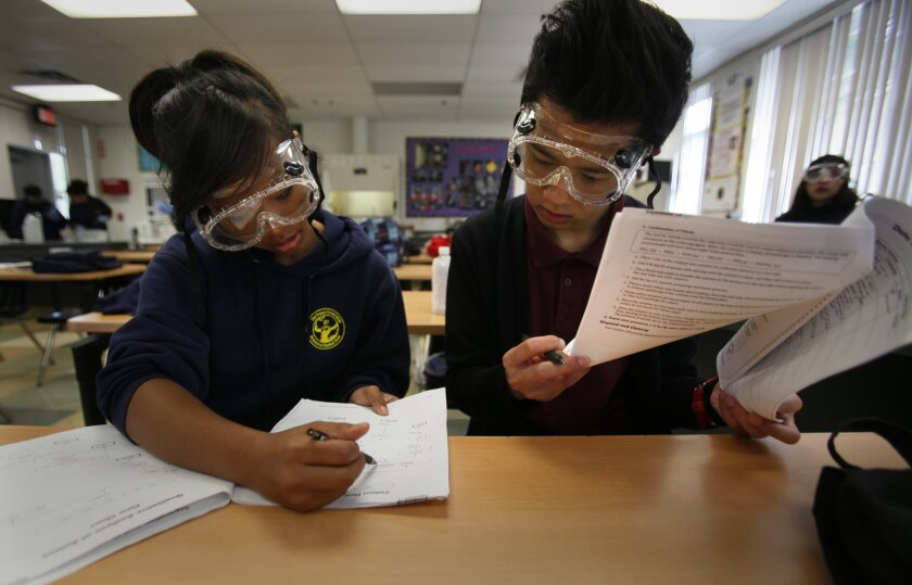 In an AP Chemistry class, Elayne Tram Nguyen, 18, left, and Destin Dao, 18, go over their notes for an experiment they were performing in class Tuesday morning. UCSD Preuss School was picked as the top charter school in California via a USC study of the state's charter school, based on performance and financial measures.