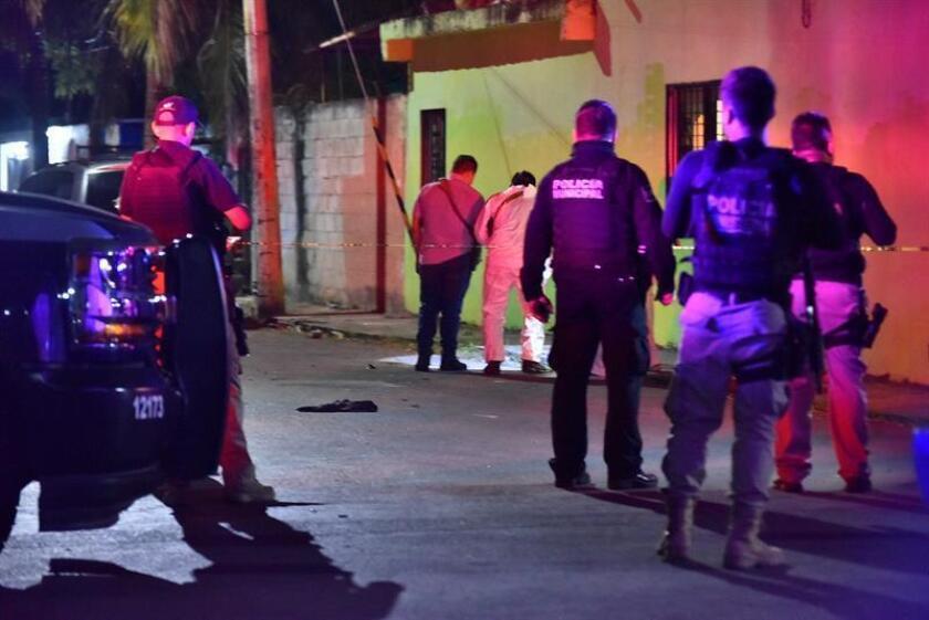 Peritos judiciales inspeccionan la zona donde se registró un ataque con armas de fuego este domingo en Cancún (México). EFE
