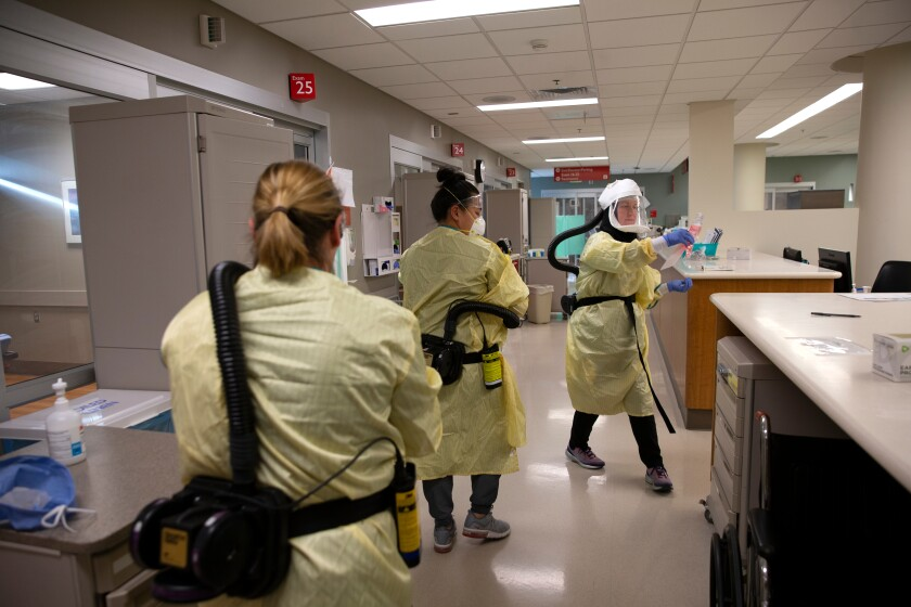 Health care workers wearing respirators as they care for COVID-19 patients in an emergency department.