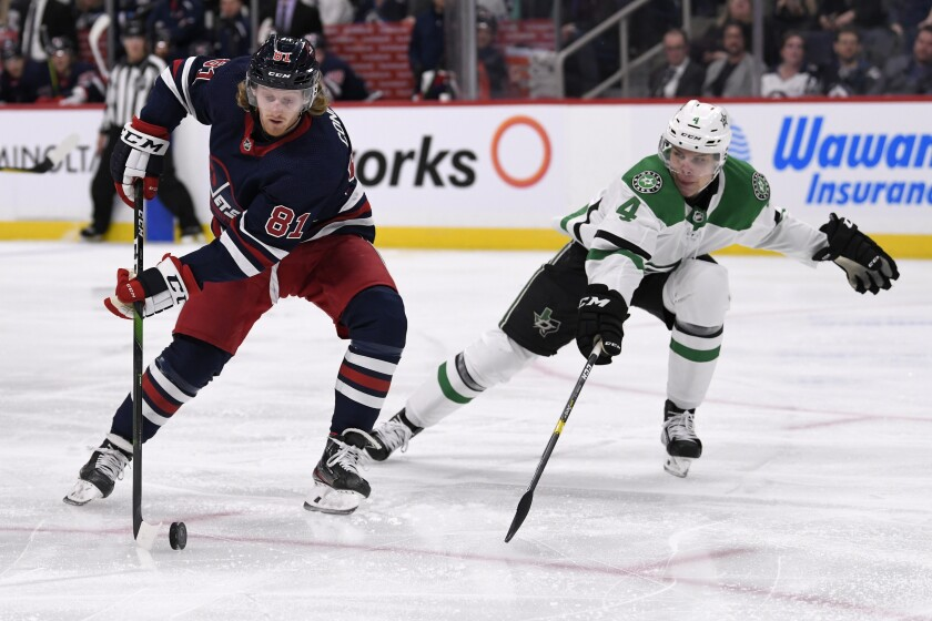 Winnipeg Jets' Kyle Connor (81) skates past Dallas Stars' Miro Heiskanen (4) during the second period of an NHL hockey game, Tuesday, Dec. 3, 2019 in Winnipeg, Manitoba. (Fred Greenslade/The Canadian Press via AP)