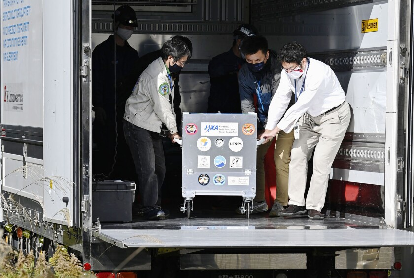 A small capsule dropped by Japans' Hayabusa2 spacecraft in a container box arrives at the Japan Aerospace Exploration Agency's research facility in Sagamihara, near Tokyo Tuesday, Dec. 8, 2020. The capsule containing asteroid soil samples that landed in the Australian Outback arrived Tuesday in Tokyo for research into the origin of the solar system and life on Earth. (Yu Nakajima/Kyodo News via AP)