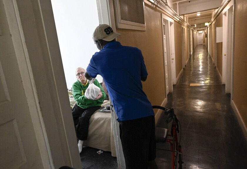 Serving Seniors driver Samond Hayes delivers a meal to Sean Smyth in San Diego.