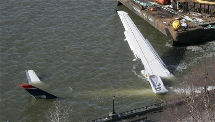 A submerged airplane that crashed into the Hudson River on Thursday and was towed to the west side of Manhattan for further inspection is shown Friday, Jan. 16, 2009, in New York. Investigators brought in a giant crane and a barge Friday to help pull a US Airways jetliner from the Hudson River, and