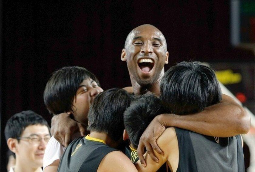 Kobe Bryant hugs South Korean fans during a promotional tour through Asia during the 2011 offseason.