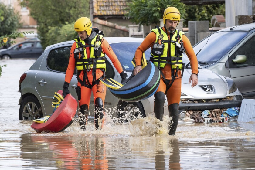 Rescue workers wade through muddy waters searching for survivors in the town of Trebes, southern France,