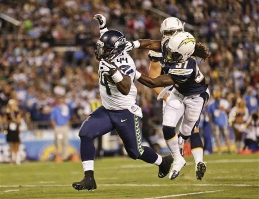 Seattle Seahawks running back Spencer Ware drags San Diego Chargers defensive back Jahleel Addae in to the end zone while scoring a six yard touchdown in the third quarter of an NFL preseason football game Thursday, Aug. 8, 2013, in San Diego. (AP Photo/Gregory Bull)