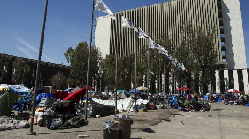Homeless individuals gather at an encampemnt at the Santa Ana Civic Center near the Orange County Co
