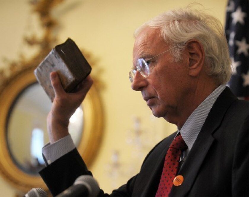 German Ambassador Klaus Scharioth held up one of the books recovered by Robert Thomas during World War II. (Bill O'Leary / The Washington Post)
