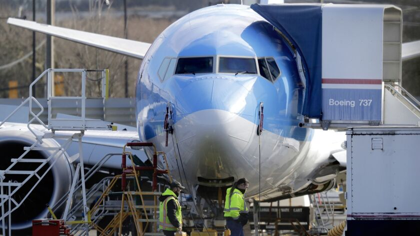 Workers walk past a 737 Max 8 airplane being built at Boeing Co.'s assembly plant in Renton, Wash.